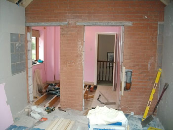 View from the garage extension into existing small bedroom to be converted into en-suite shower room and door recess